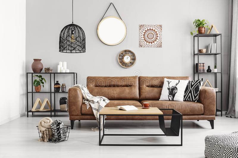 Leather sofa with pillows and blanket in elegant living room interior with metal shelves and modern coffee table,. Leather sofa with pillows and blanket in the stock photo