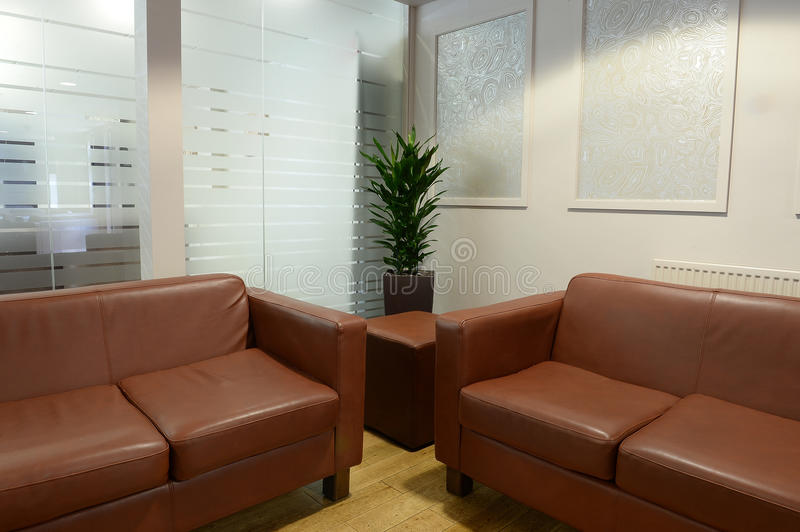 Leather sofas in modern room. Office area or home den with two brown leather sofas or couches and a glass wall stock photo