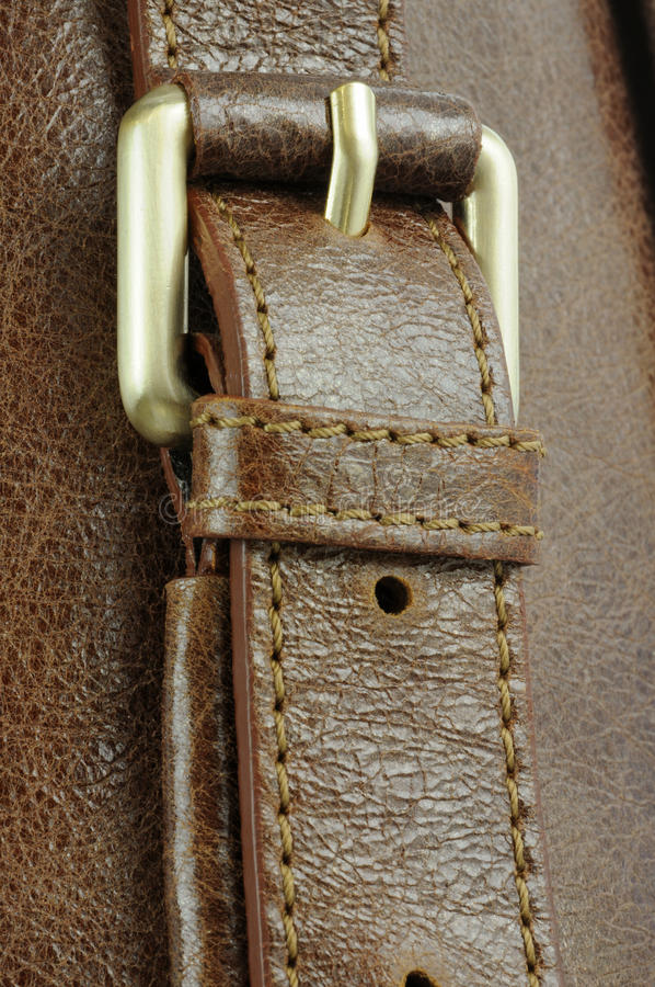 Leather strap. Gold buckle on brown leather handbag strap royalty free stock images