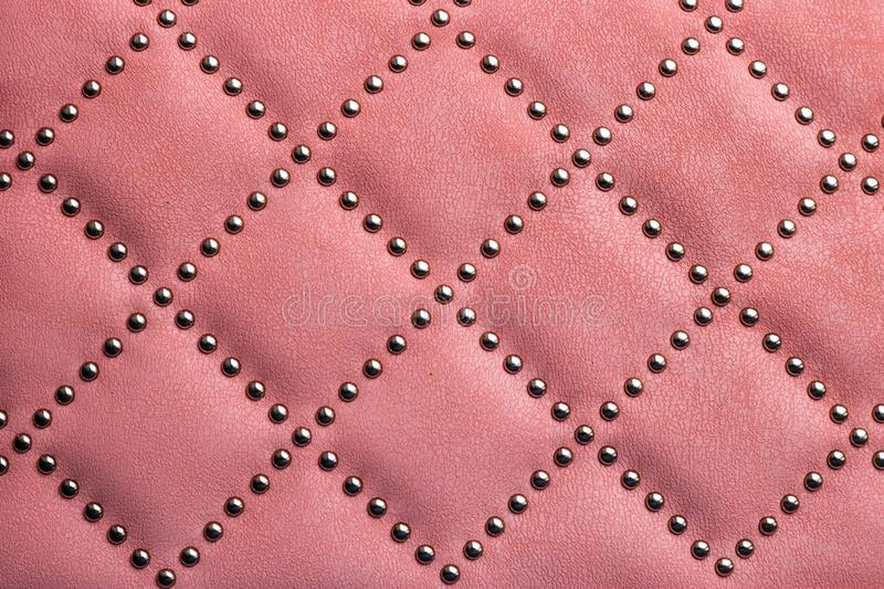 Leather texture with metal rivets. Use as background. Pink leather with metal rivets closeup as a background stock images