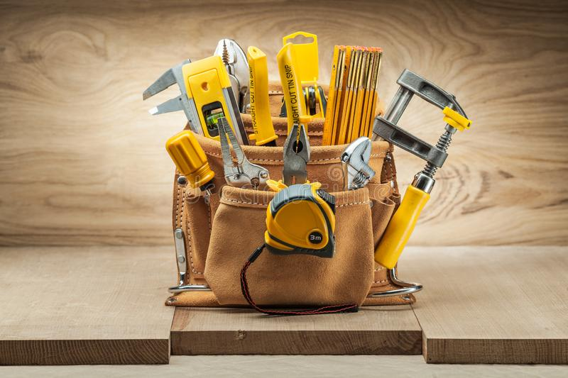 Leather tool belt with construction tools on wood backgeound stock photo
