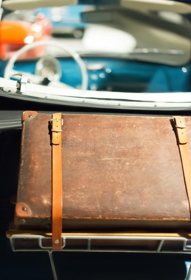 Leather travel suitcase fixed on antique car. Travel concept. Vintage style stock image