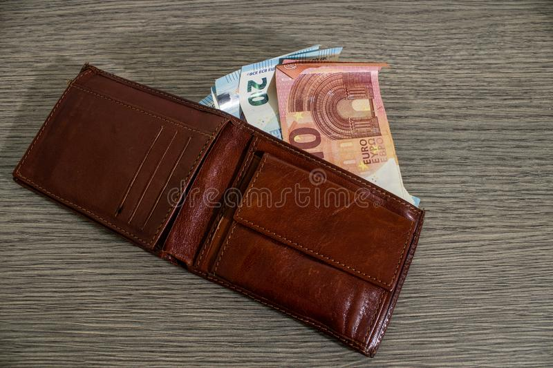 Leather wallet full of euro banknote on a decorated wood table. Composition royalty free stock images