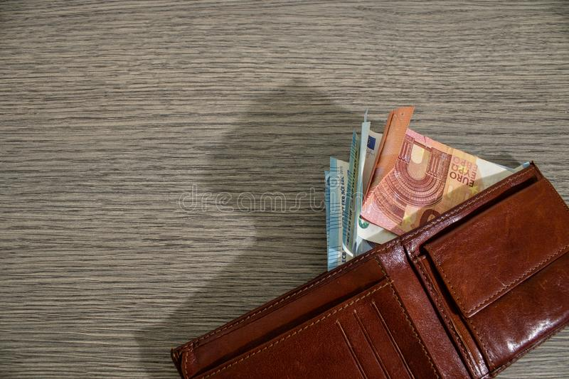 Leather wallet full of euro banknote on a decorated wood table. Composition stock photography