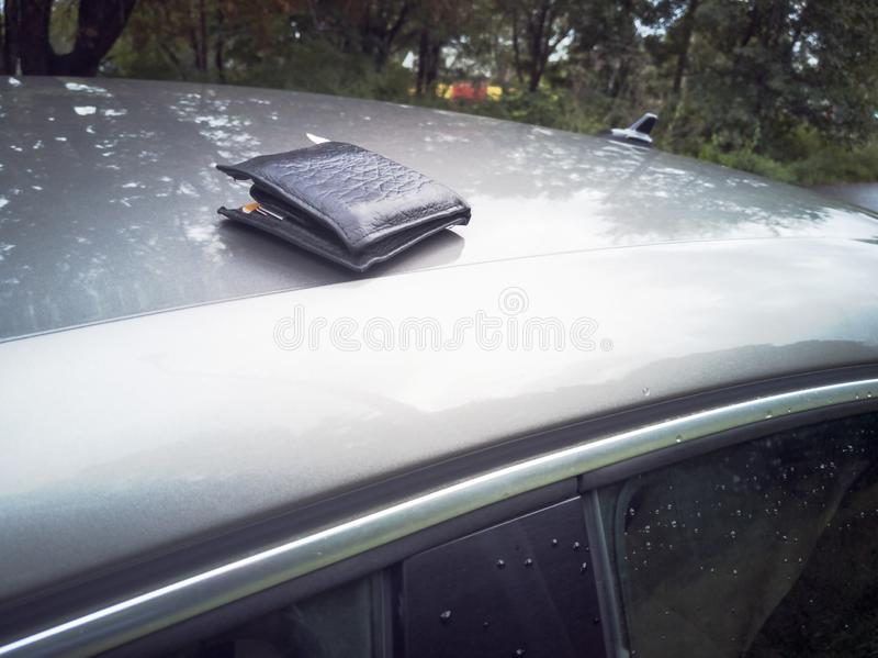 Lost Wallet with money. Leather Wallet with money and credit cards on the car vehicle roof. Lost or forgotten wallet on city street. loss concept. Real people royalty free stock photography