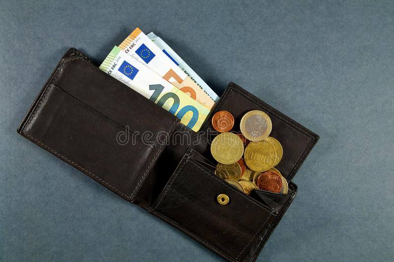 Leather wallet with a pile of euro banknotes and euro money cash coins, finance currency isolated, dark background. coins. And banknotes 100 and 50 euros in a royalty free stock photos