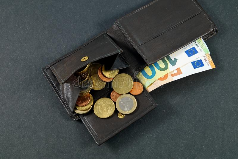 Leather wallet with a pile of euro banknotes and euro money cash coins, finance currency isolated, dark background. coins. And banknotes 100 and 50 euros in a stock images
