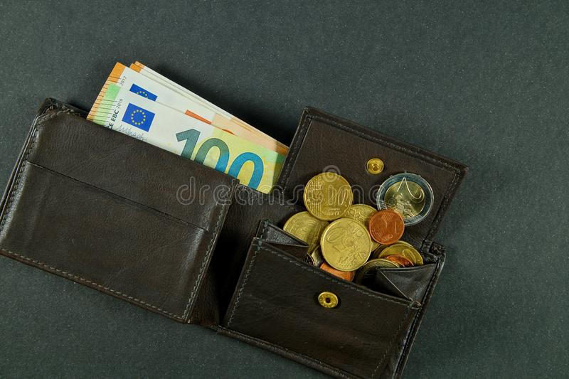 Leather wallet with a pile of euro banknotes and euro money cash coins, finance currency isolated, dark background. coins. And banknotes 100 and 50 euros in a royalty free stock photo