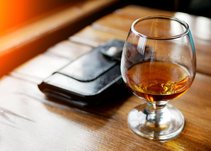 Leather wallet, red wine glass and cash spread out a table, concept of alcohol abuse and waste of money stock photo