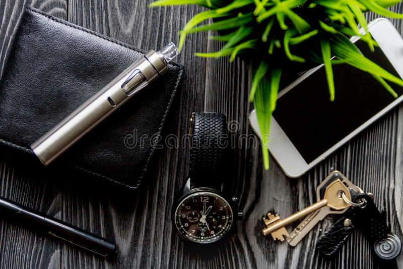 Leather wallet, watch, electronic cigarette dark wooden background top view. Leather wallet, watch, electronic cigarette on dark wooden background top view stock photo