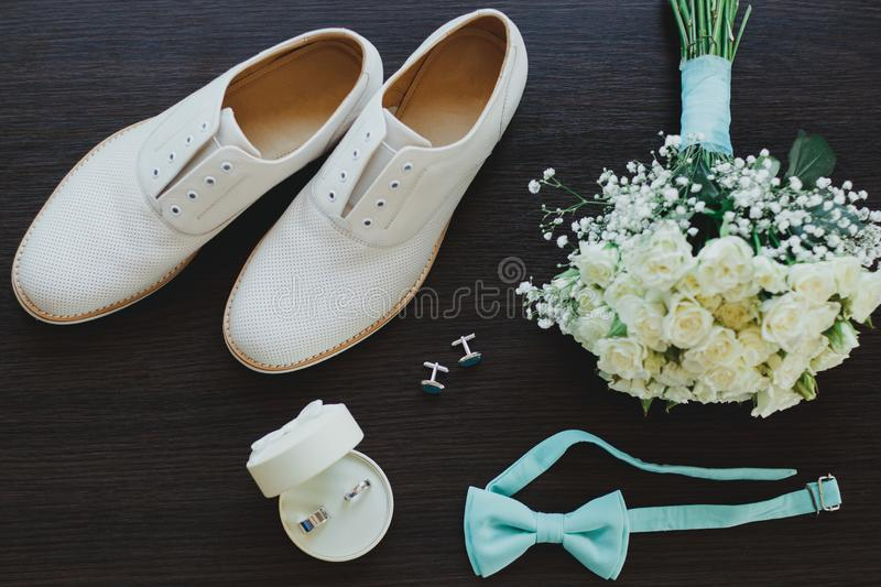 Leather white groom wedding shoes on the wooden background in sun rays. Rings, bow tie and cufflinks with elegant bouquet. Elegant royalty free stock image