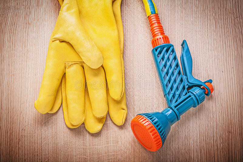 Leather working gloves garden rubber hose nozzle on wooden board. Gardening concept stock photos