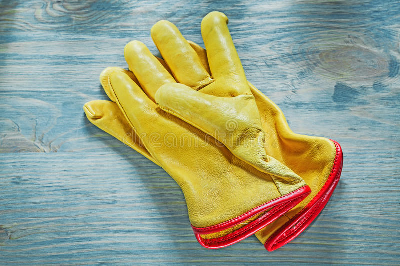 Leather working gloves on wooden board top view construction con. Cept royalty free stock photography