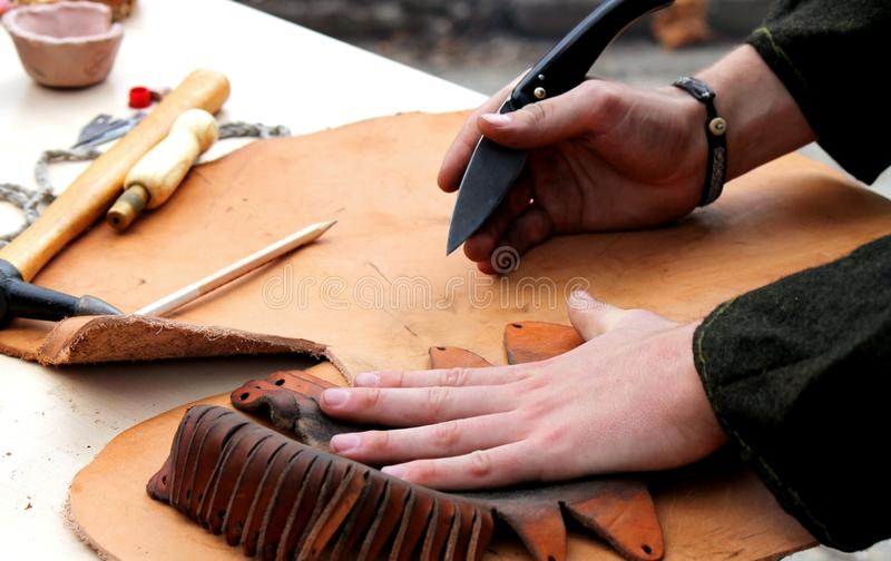 Leather working. A professional re-enactment craftsman making leather shoes like how it was done in the past stock photo