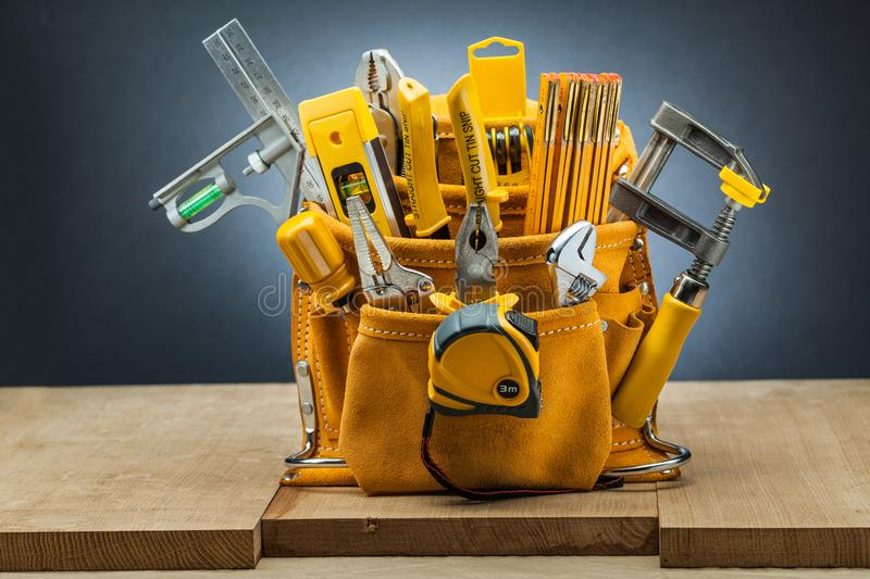 Leather working tool belt with many construction tools royalty free stock images