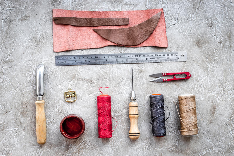 Leather workshop. Tanner`s tools on grey stone background top view.  stock photography
