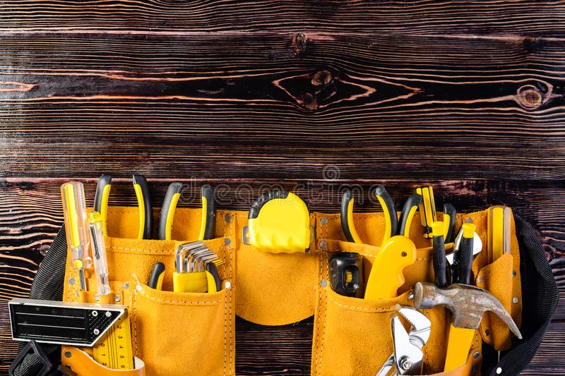 Leather yellow tool belt with construction tooling on brown wood royalty free stock photos