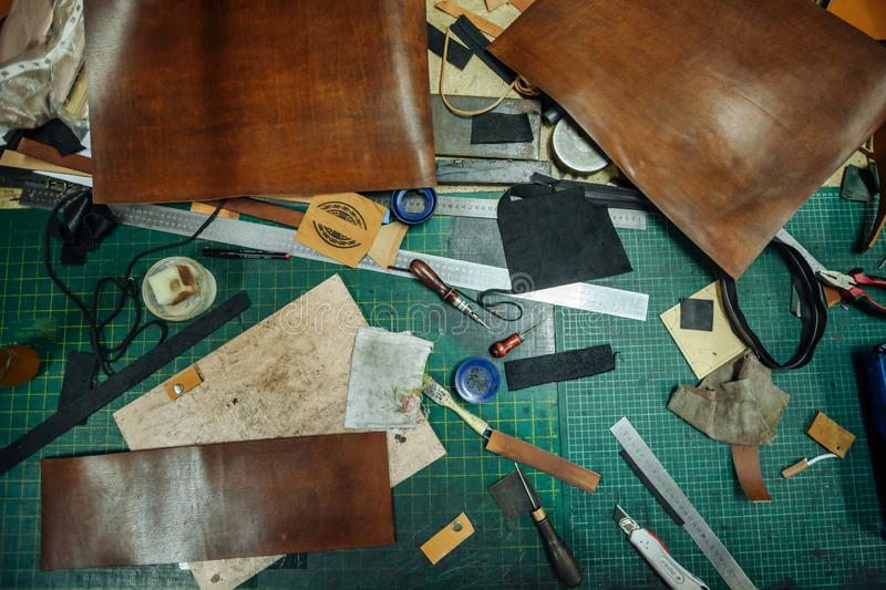 Leatherworking tools. Riveter, awl, ruler, pliers, tassels, pencil, leather pieces, rivets and fasteners are on the royalty free stock photography