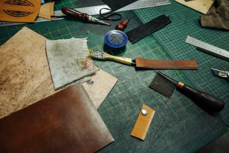 Leatherworking-Werkzeuge Nieteneinschläger, Ahle, Machthaber, Zangen, Quasten, Bleistift, lederne Stücke, Niete und Befestiger si stockfotografie