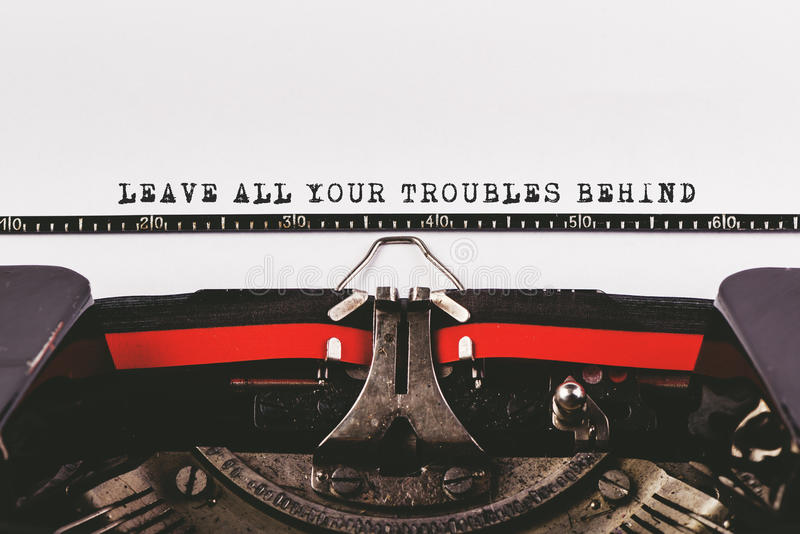 Leave all your troubles behind. Motivationl message typed on old typwriter machine stock photo
