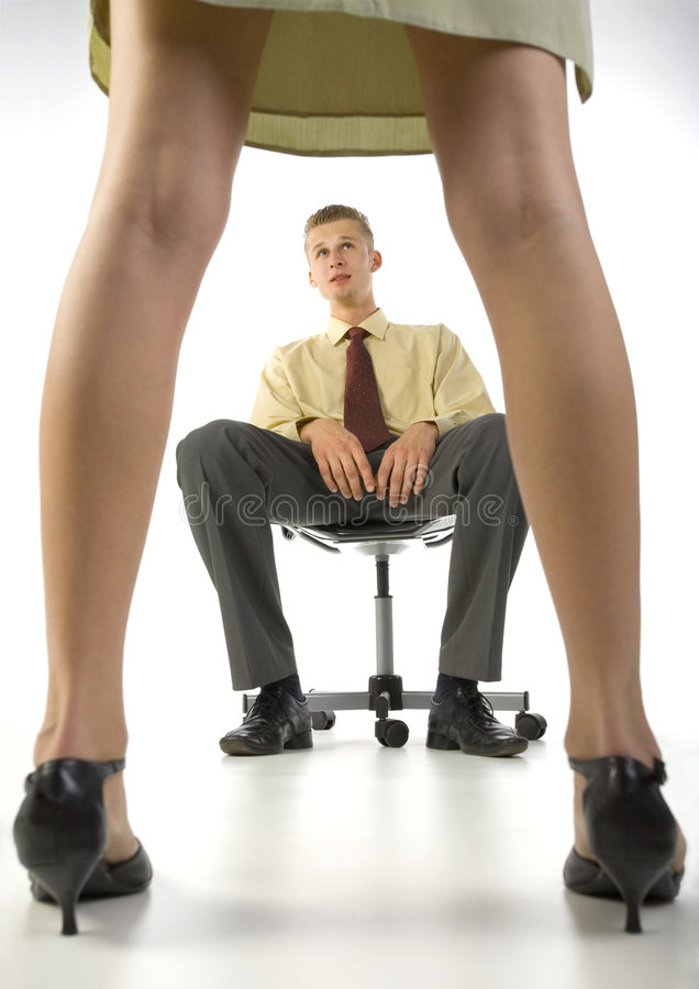 Leave me alone... Young, scared businessman, sitting on chair in front of woman in skirt. White background royalty free stock images