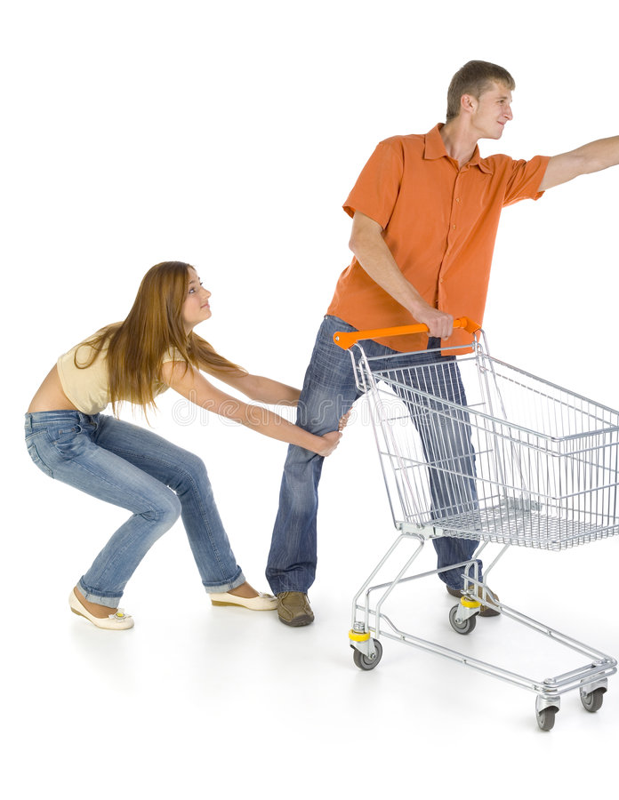 Leave me alone!. Young couple with trolley. Girl is holding boy's leg and begging for something. Isolated on white in studio. Whole body stock images