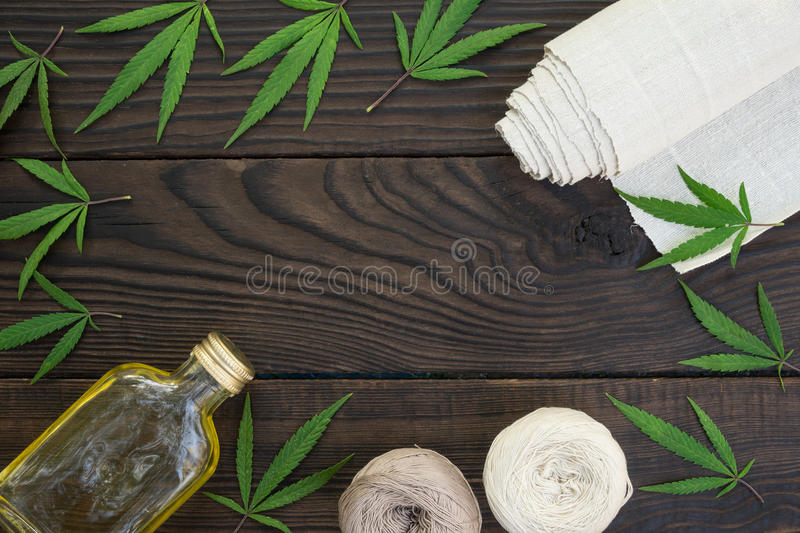 Leaves of cannabis, a bottle of hemp oil and tangles of thread o royalty free stock photography