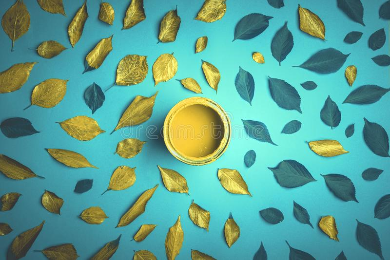 Golden leaves on a blue cyan background. Leaves painted in yellow golden color above view. Golden leaves on a blue cyan background. Can with yellow wood paint royalty free stock photos