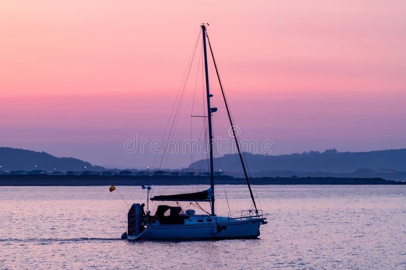 Leaving Porthcawl Harbour at Dawn. A yacht sails out of Porthcawl harbour at dawn on a calm, high tide royalty free stock photos