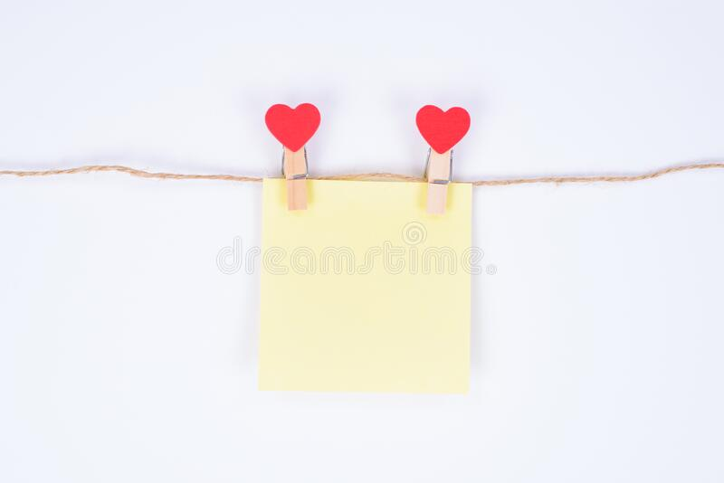 Leaving secret congrats concept. Close up photo of small yellow paper sticker hanging on a rope attached with heart shaped. Clothespins isolated white stock photo