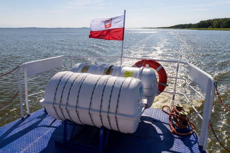 """Leba pomorskie/lipca 2019 för Polska †""""14: Polsk flagga inställd på aktern av ett litet inlands- skepp En skyttel som svävar på royaltyfria bilder"""
