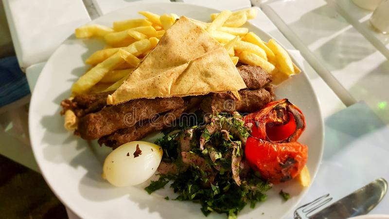 Lebanese kebab with onions, tomatoes, french fries and Lebanese bread. Lebanon. June, 2019 stock image