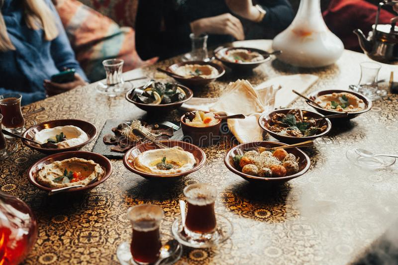 Lebanon cuisine served in restaurant. A young company of people is smoking a hookah and communicating in an oriental restaurant. T stock photo