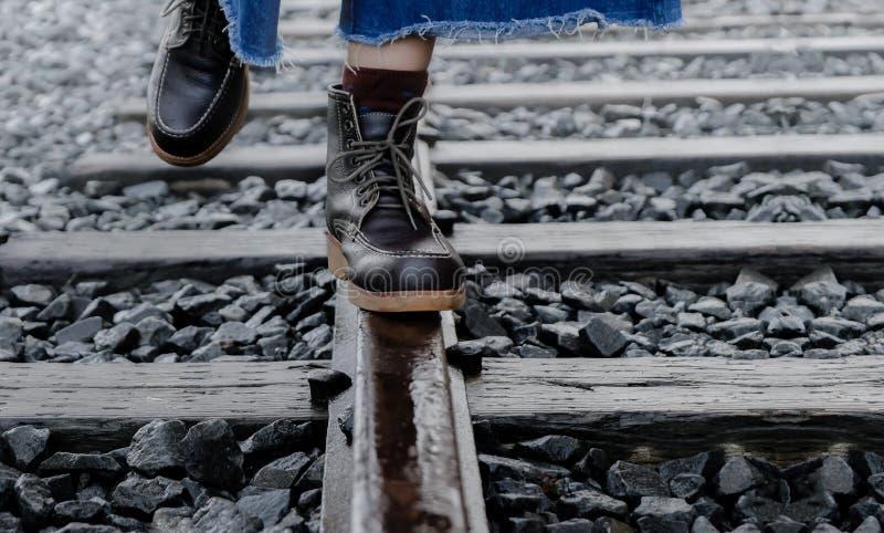 Leben-Balancenkonzept Eine junge Frau, die zum Balancieren ihres Körpers auf dem Schienenstrang versucht stockbild