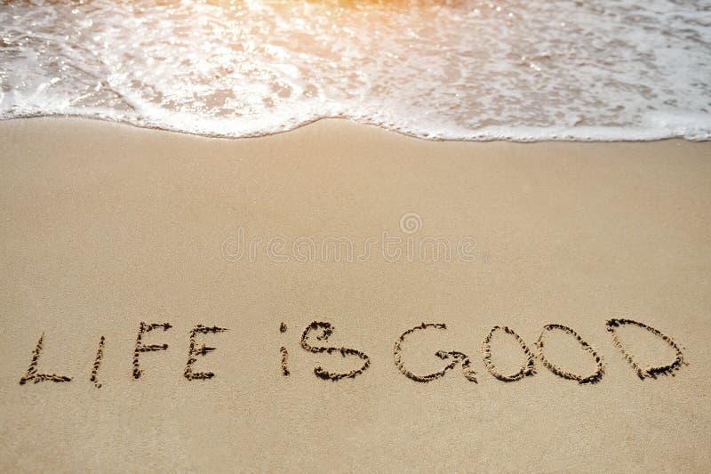 Leben in gutem geschrieben auf Sandstrand - positives denkendes Konzept stockfoto