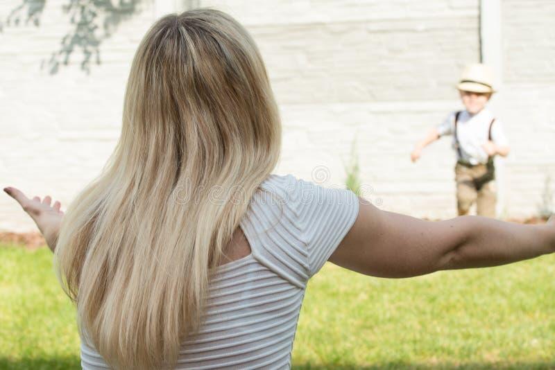 Lebenmoment der gl?cklichen Familie! Mutter- und Sohnkind, das zusammen Spa? auf dem Gras habend im sonnigen Sommertag spielt lizenzfreie stockbilder