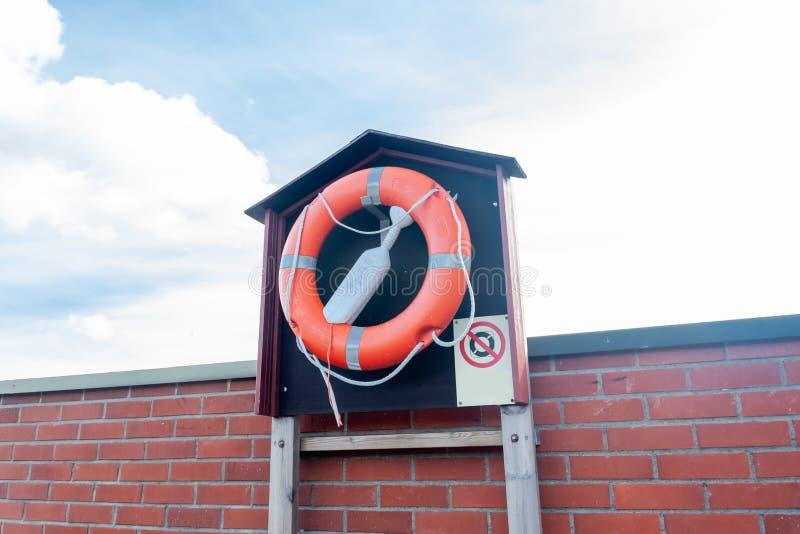 Lebens-Bojenring auf der hölzernen Pier- und Backsteinwand stockfotos