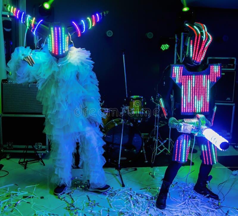 Lebensgroße Marionetten in Form von Robotern auf einem Stadium Lustiger Amateurtanz stockfotografie