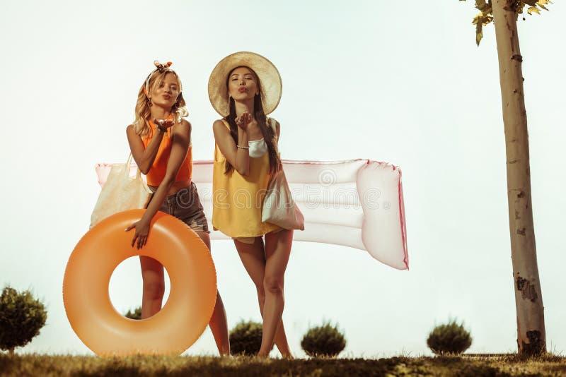 Lebensgroßes Foto von den Mädchen, die schwimmendes Material halten und Küsse senden lizenzfreies stockfoto
