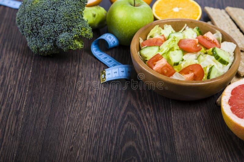 Lebensmittel für Diät und messendes Band auf einem dunklen Holztisch lizenzfreie stockfotos