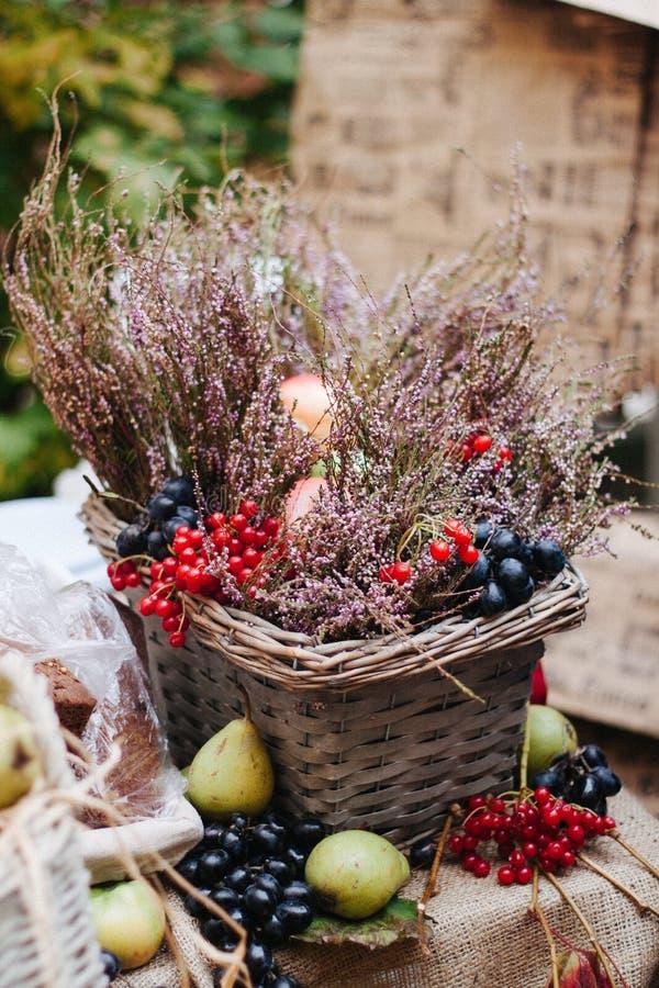 Lebensmittel-Fotografie-Korb mit Blumen, Beeren und Birnen auf dem Tisch stockbild