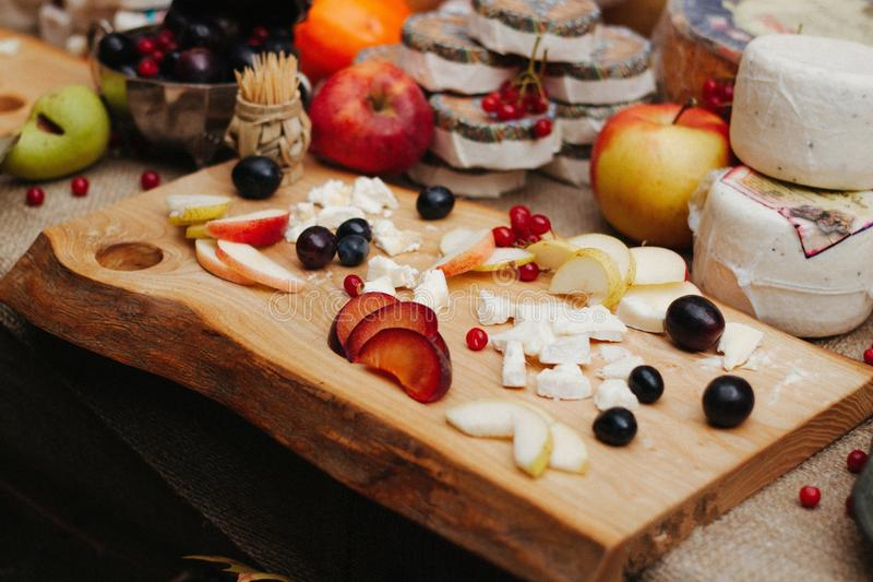 Lebensmittel-Fotografiekäse, -beeren und -scheiben des Pfirsiches und der Äpfel auf dem hölzernen Brett lizenzfreies stockfoto