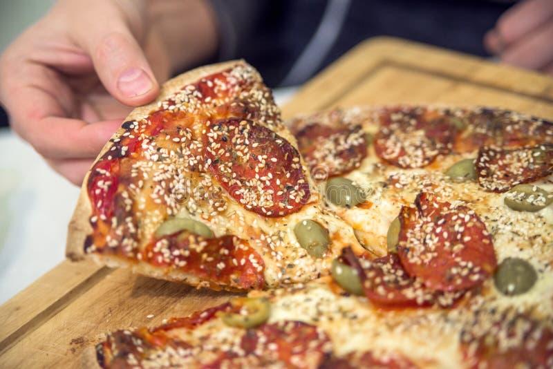 Lebensmittel, italienische Küche und oben essen Konzept - nah von der Hand, die selbst gemachte Pizza auf Holztisch nimmt und tei lizenzfreie stockfotos