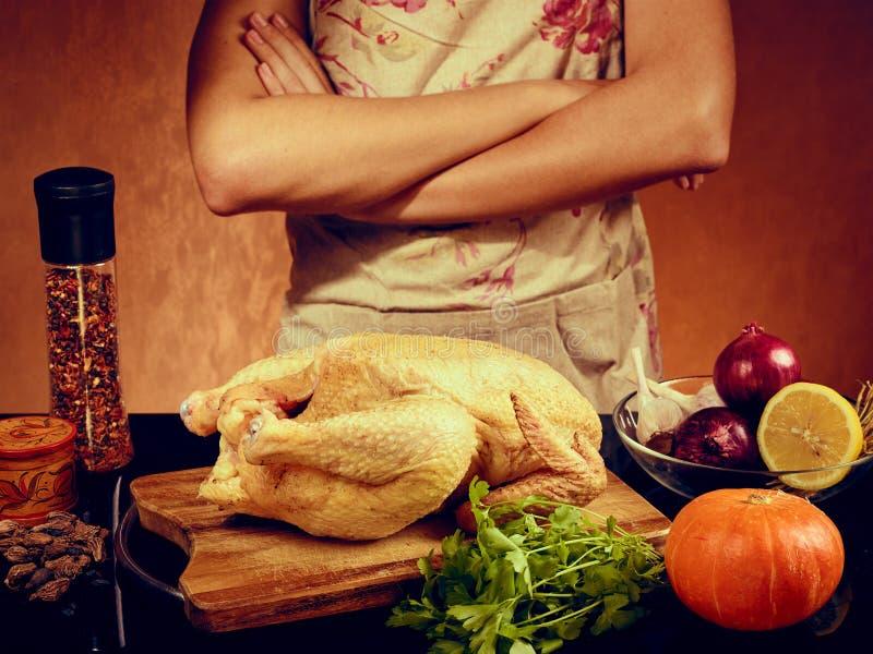Lebensmittelfoto des unerkennbaren Mannes Huhn im kitchencook im Schutzblech auf orange Hintergrund kochend stockbilder