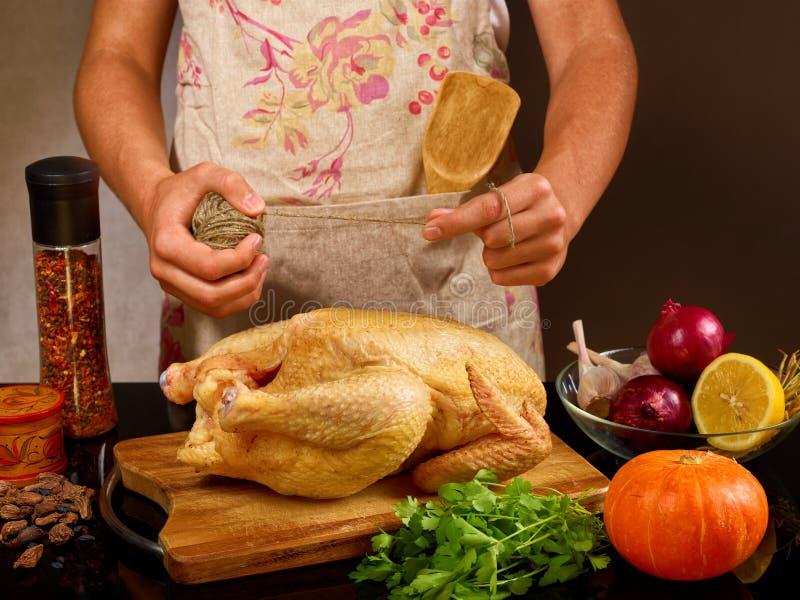 Lebensmittelfoto des unerkennbaren Mannes Huhn im kitchencook im Schutzblech mit Seil kochend lizenzfreies stockbild