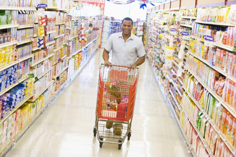 Lebensmittelgeschäfteinkaufen des jungen Mannes lizenzfreies stockbild