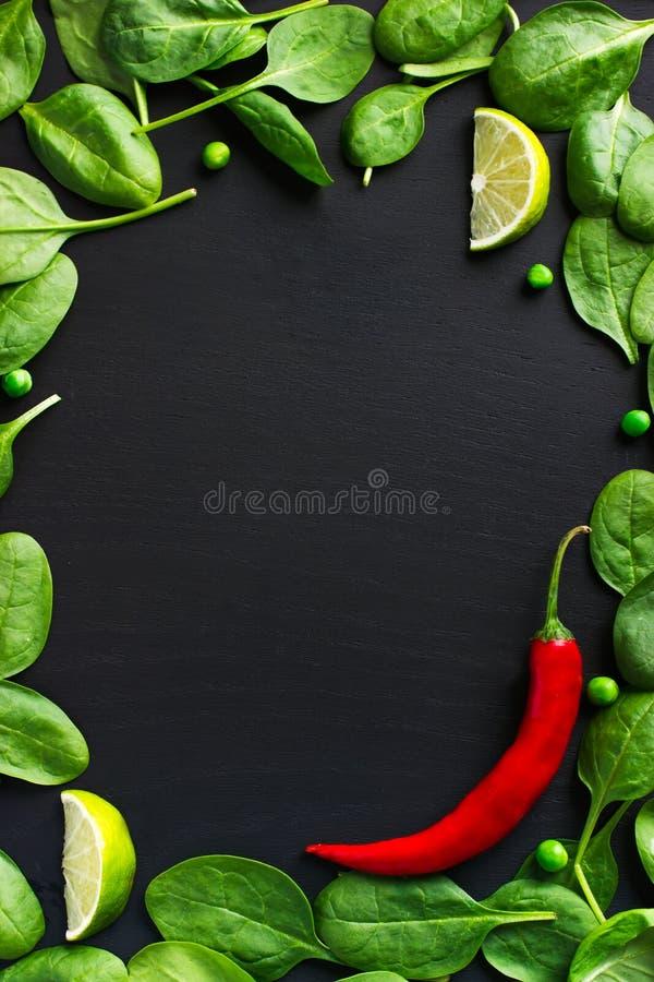 Lebensmittelhintergrund mit Pfeffer des Spinats und des roten Paprikas stockfotografie