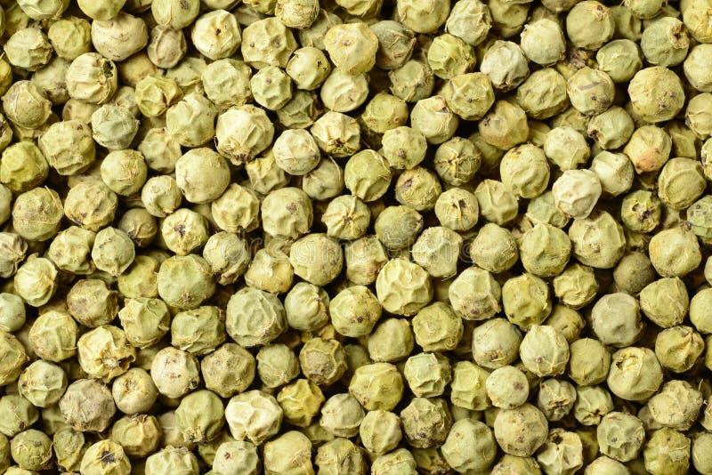 Lebensmittelhintergrund von getrockneten grünen Pfefferkörnern, Draufsicht lizenzfreies stockbild
