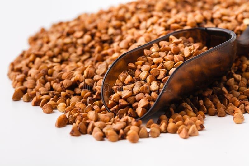 Lebensmittelinhaltsstoffe: Haufen des Buchweizens in einer h?lzernen Schaufel, auf wei?em Hintergrund stockfotografie