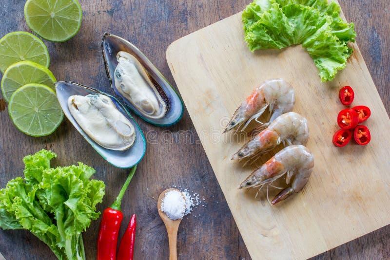 Lebensmittelinhaltsstoffhintergrund Neuseeland-Miesmuschel, Garnele, Pfeffer, Salat, Salz, hölzerner Plattenkalk oder Zitrone auf stockfotos